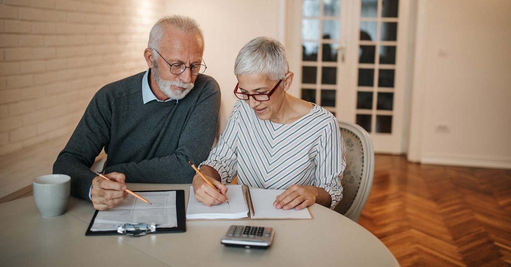 kuvassa vanhempi pariskunta pöydän ääressä. artikkeli käsittelee käänteistä asuntolainaa